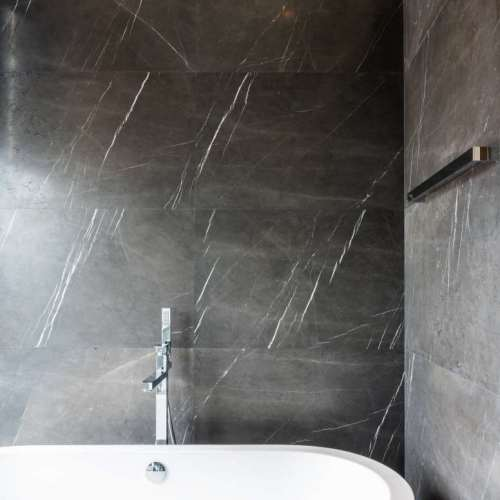 modern-bathroom-interior-with-bathtub-and-brown-natural-marble-wall-interior-design-copy-space-min