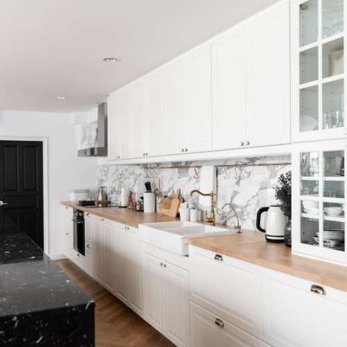 modern-classic-kitchen-interior-with-kitchen-appliances-and-white-ceramic-sink-with-gold-mirror-faucet-on-wood-top-with-marble-wall-min
